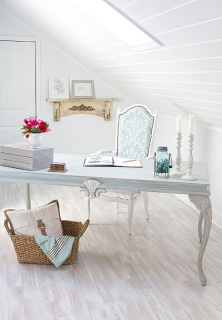 a vintage attic home office with white walls and a ceiling plus a whitewashed floor and vintage furniture