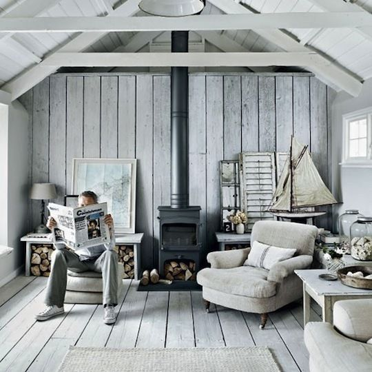 a neutral coastal living room with whitewashed walls, a ceiling, a floor and comfy furniture with a vintage feel