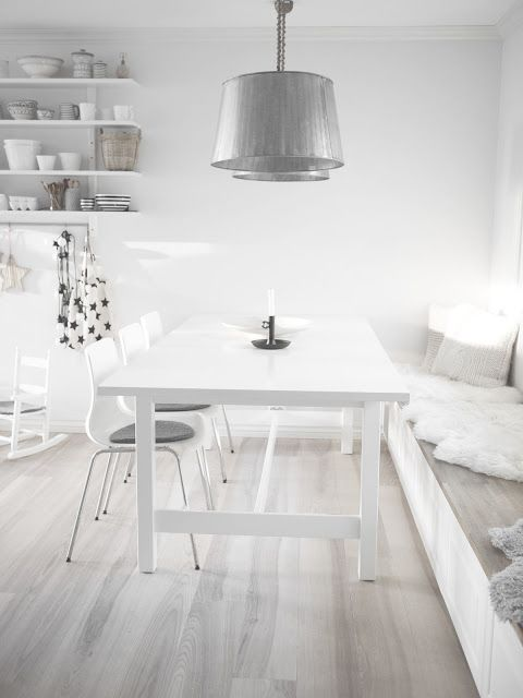 an all white room with a whitewashed floor and metallic touches is airy, light filled and very fresh