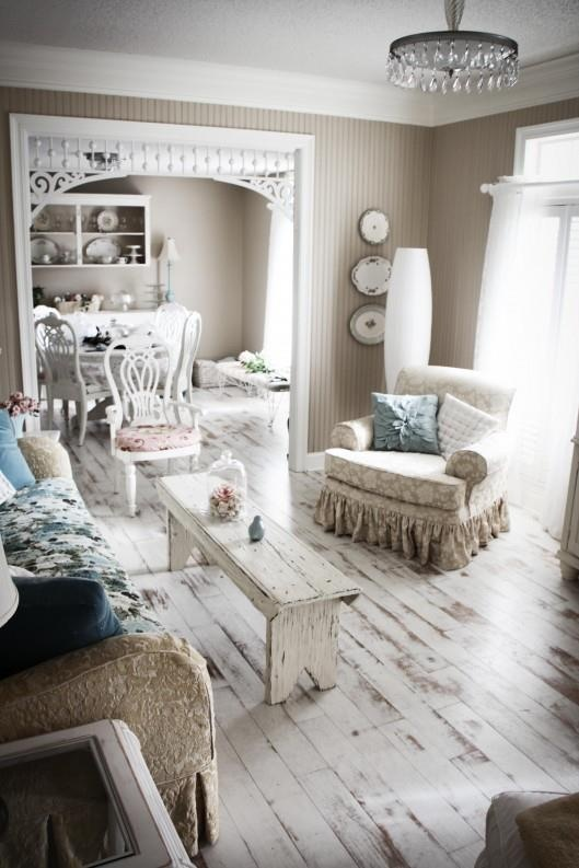 a shabby chic living room with whitewashed wooden floors, white vintage furniture and pastel textiles