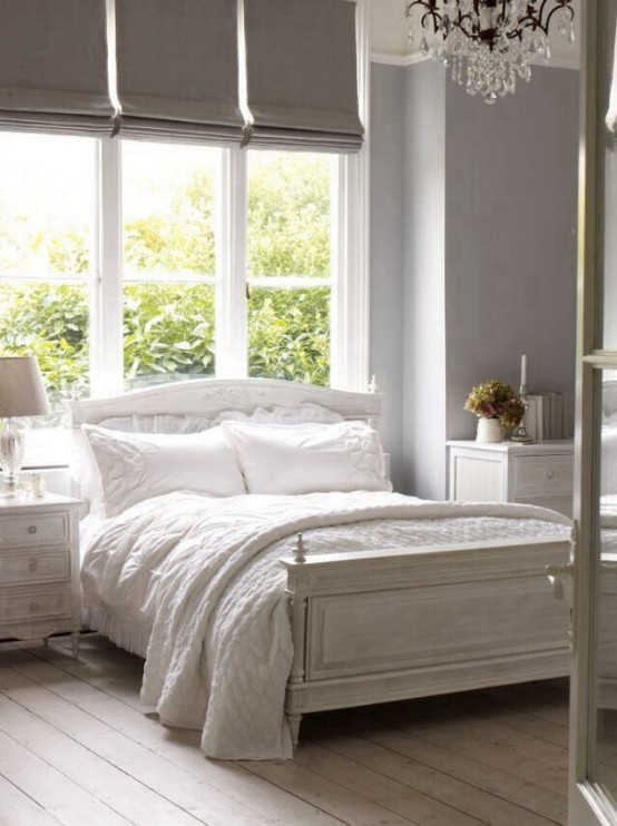 a white shabby chic bedroom with whitewashed floors and furniture is delicate and vintage-inspired