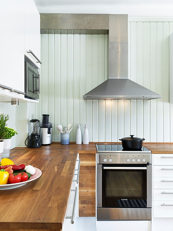 rich stained butcherblock countertops bring a rustic feel to this farmhouse kitchen and make it look cozier and warmer