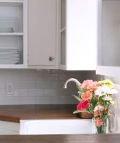 dark stained wooden countertops contrast the white kitchen and make it bolder and outstanding