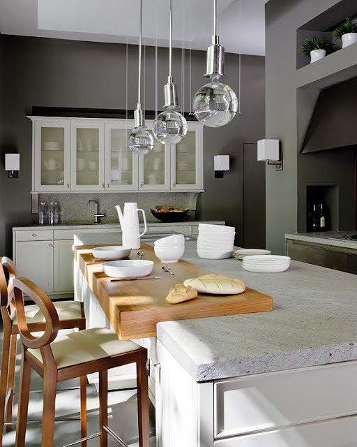 a white stone countertop paired with a sleek wooden part divide the cooking and meal zone easily