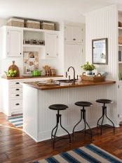 a white farmhouse kitchen with rich stained countertops that contrast the space and make it bold and cozy
