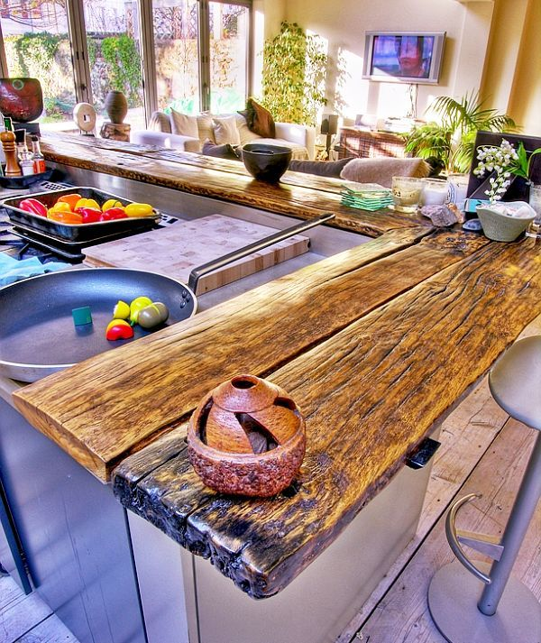 a rough and weathered wood slab kitchen countertop is a very cool idea to add a rustic touch to the space
