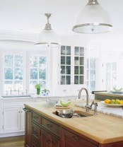 a white farmhouse kitchen with a contrasting kitchen island – a dark stained vintage piece with light stained butcherblock countertops looks really chic