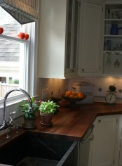 a neutral farmhouse kitchen with rich stained butcherblock countertops that contrast it and make it bold and dramatic