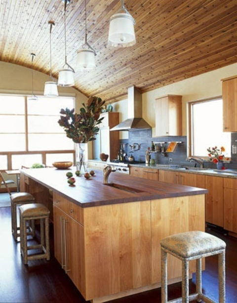 a chalet kitchen clad with wood, with stone countertops and a wooden kitchen island with rich stained countertops that contrast the space and makes it interesting