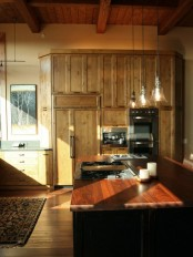 a dark kitchen island with a rich stained wooden countertop adds chic and coziness to the kitchen making it more dramatic