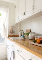 a simple and neutral modern farmhouse kitchen with light stained butcherblock countertops that enliven the space and warm it up