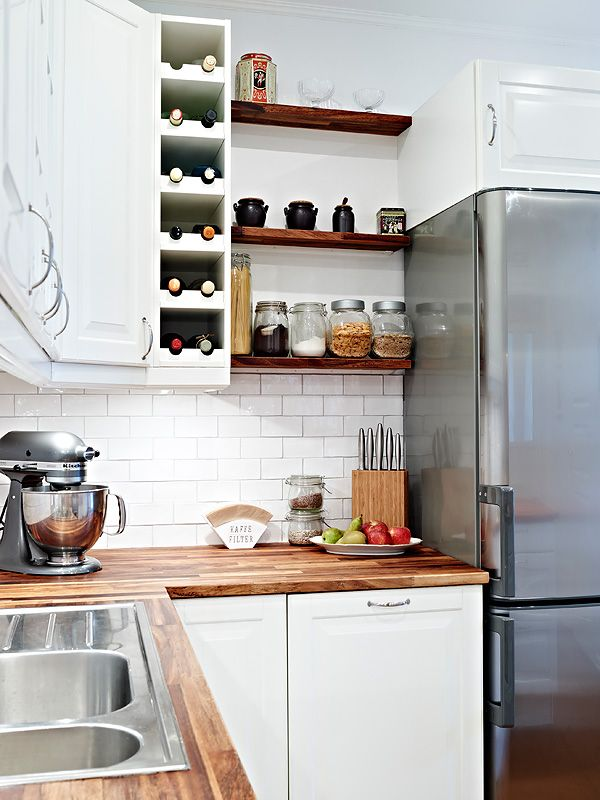 a modern white kitchen with butcherblock countertops and dark stained open shelves that echo with them