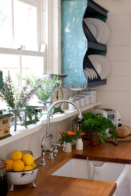a white kitchen spruced up with rich stained wooden countertops and a blue shabby chic open shelving unit