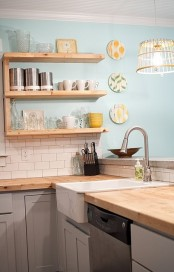 a dove grey kitchen with light stained wooden countertops and wall mounted shelves that match