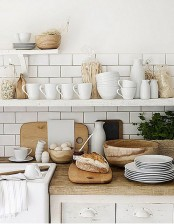 a white Nordic kitchen with light stained wooden countertops, wooden bowls and baskets for a cozy feel