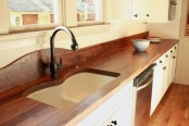rich stained butcherblock countertops and matching floors add warmth and coziness to the kitchen