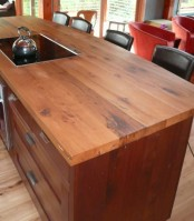 a dark stained kitchen with a rich stained wooden countertop is a cool idea to warm up the space and make it more welcoming