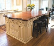 a neutral vintage kitchen island with a dark stained wooden countertop for elegance and chic in the space