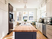 a modern neutral kitchen with a blue kitchen island and butcherblock countertops to contrast the space