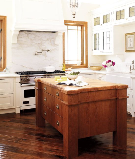 a vintage wooden kitchen island with matching coutnertops is a bold contrasting furniture piece to enliven a white kitchen