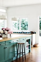 a turquoise kitchen island with a light stained wooden countertop that contrasts the kitchen around it and looks super bold