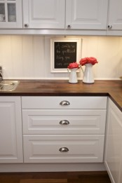 dark stained wooden kitchen countertops contrast the white cabinets and add a dramatic touch to the space