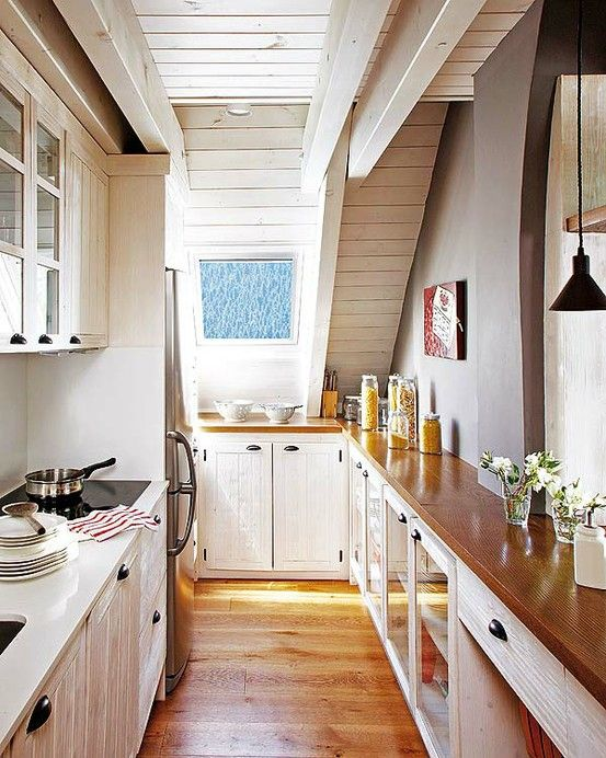 a white farmhouse kitchen enlivened with rich stained countertops looks inviting and very cozy