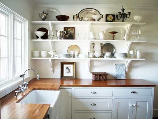 a white farmhouse kitchen with rich stained butcherblock countertops is a stylish space with a bold look