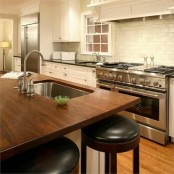 a white vintage kitchen and an oversized kitchen island with a dark stained wooden countertop that contrasts the space and makes a statement