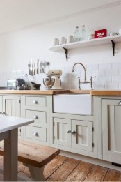 light stained wooden countertops paired beautifully with olive green cabinets create a stylish farmhouse look