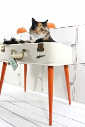 a suitcase cat bed on tall legs is a very creative idea, you can buy a ready one or make it yourself upcycling an old suitcase
