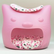 a pink cat head shaped bed or cat house with a colorful cushion inside and on top as two cat beds