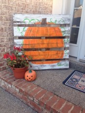 a fall pumpkin sign, a potted flower and a Jack-o-lantern for decorating your front porch