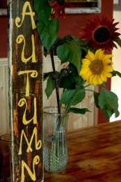 a shabby chic autumn sign and sunflowers next to it for a relaxed rustic fall look