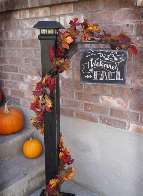 a chic chalkboard sign with fake leaves and bright pumpkins next to it is a very cool and bold idea