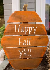 a rustic fall sign shaped as a pumpkin and painted orange plus white letters is a simple and cool craft