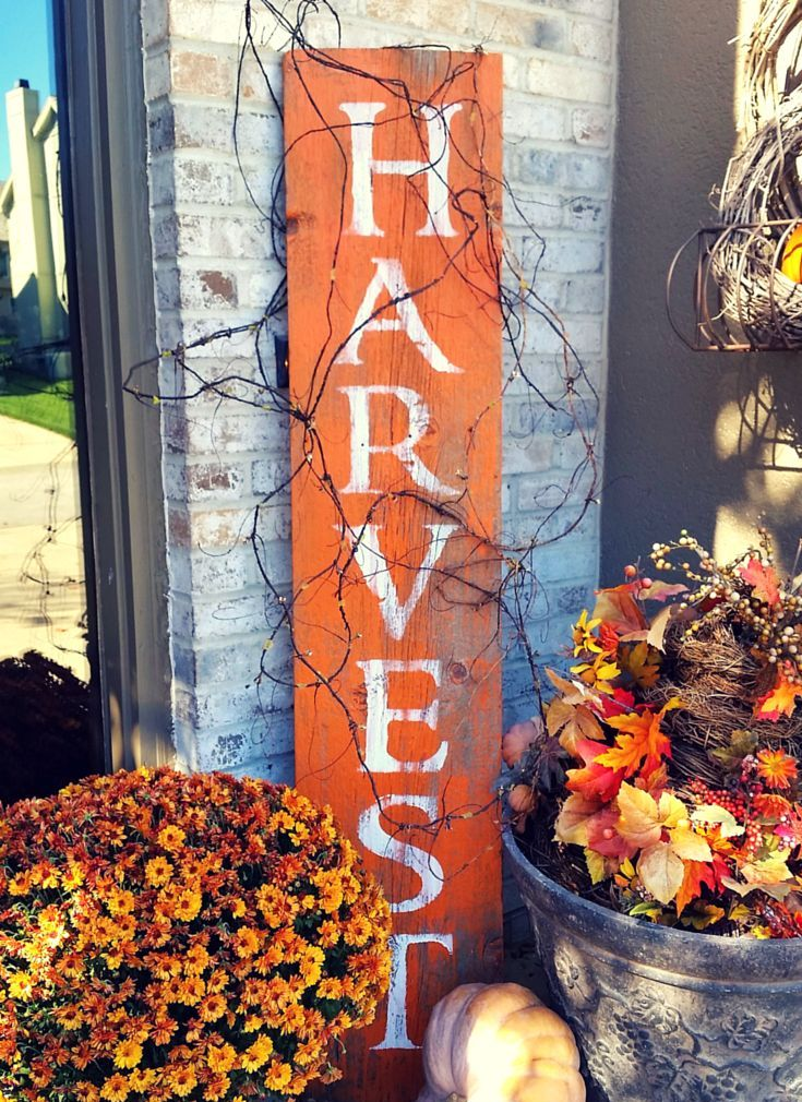 a bright orange fall sign and fall blooms and berries arranged in buckets and bathtubs