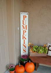 a simple Pumpkins For Sale sign surrounded with bright fall blooms and bright pumpkins will spruce up your fall porch
