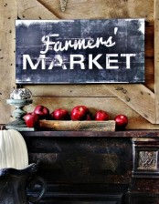 a large chalkboard sign and a wooden bowl with red apples under it is a cool idea with a farm feel