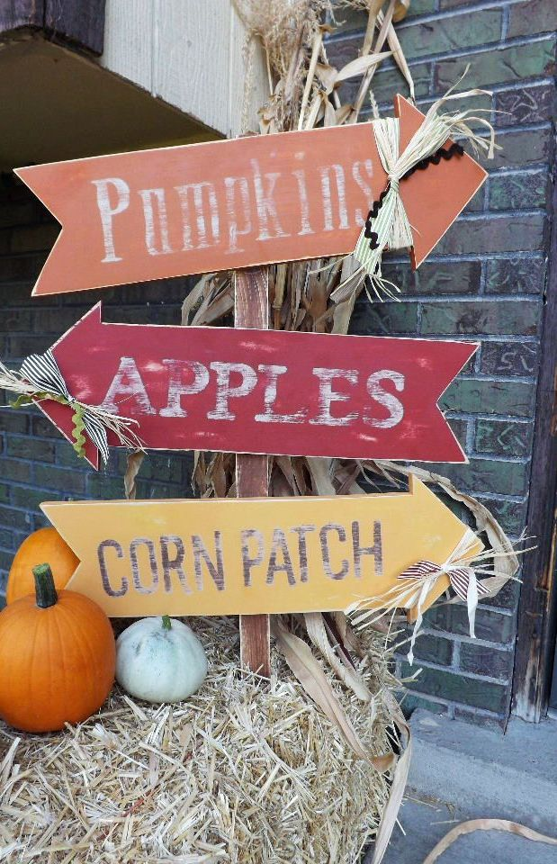 a whole bunch of fall signs in yellow, burgundy and orange, pumpkins and hay as a base