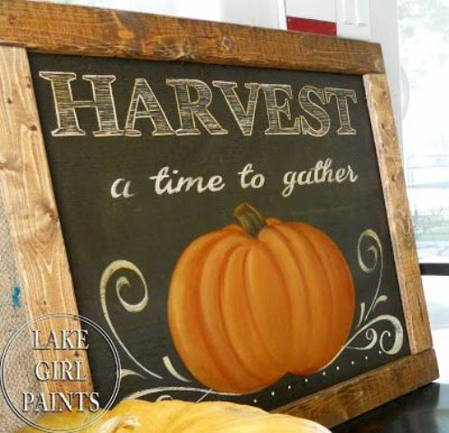 a chalkboard sign with white letters and a painted pumpkin in a simple stained wooden frame is a cool fall decoration