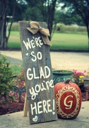 a reclaimed wood sign with a burlap bow and a painted pumpkin for a rustic fall touch to the space