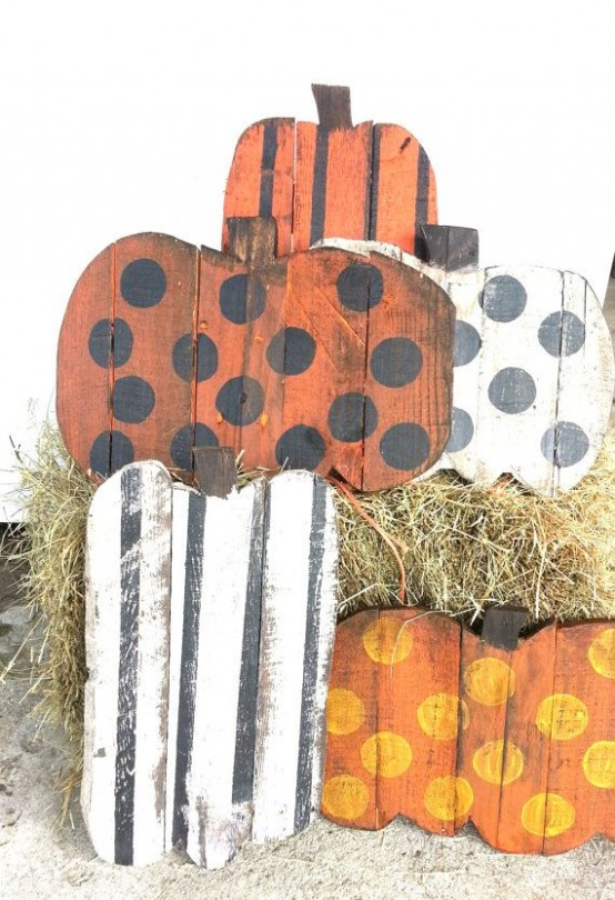 several colorful fall pumpkin signs with various shades and prints and hay for a rustic fall look