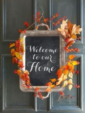 a chalkboard sign made of a tray and decorated with bold fall leaves looks amazing