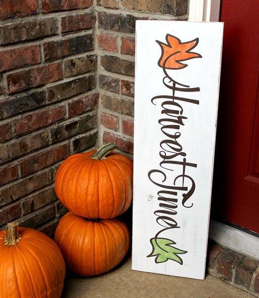 a white fall sign with colorful leaves and bright orange pumpkins for decorating your porch