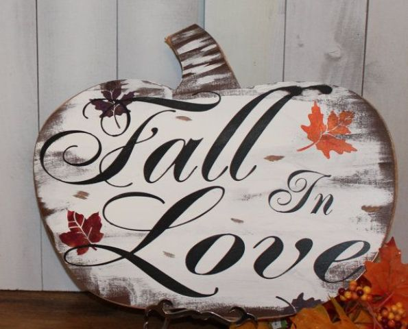 a pumpkin shaped fall sign with black letters and fall leaves is a cute piece with an unusual shape