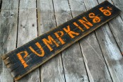 a black plank sign with orange letters is a fun and cool idea to accent your fall outdoor space