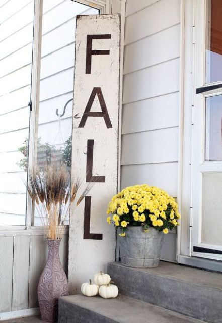a neutral and tall fall sign with grasses in vases, pumpkins and yellow blooms in a bucket