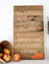a beautiful wood plank sign with pumpkins and fall leaves plus a wooden basket with apples next to it