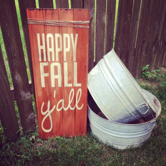 a bright orange fall sign and some buckets next to it to create a relaxed rustic fall feel
